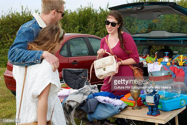 Woman selling purse from car trunk