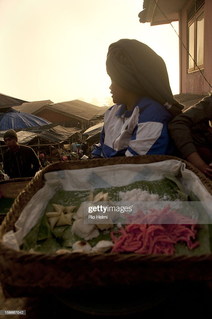 MARKET, KINTAMANI, BALI, INDONESIA - : A woman selling traditional sweet rice cakes at sunrise in the market of Kintamani.