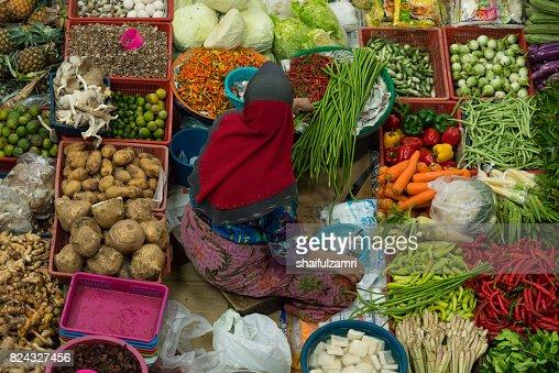 A woman selling various vegetables and local foods at Kota Bharu Main Market or famously known as Pasar Siti Khadijah : Stock Photo