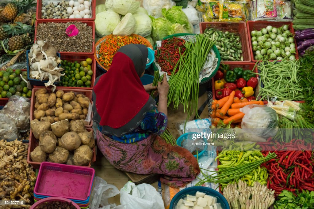 A woman selling various vegetables and local foods at Kota Bharu Main Market or famously known as Pasar Siti Khadijah : Stock Photo