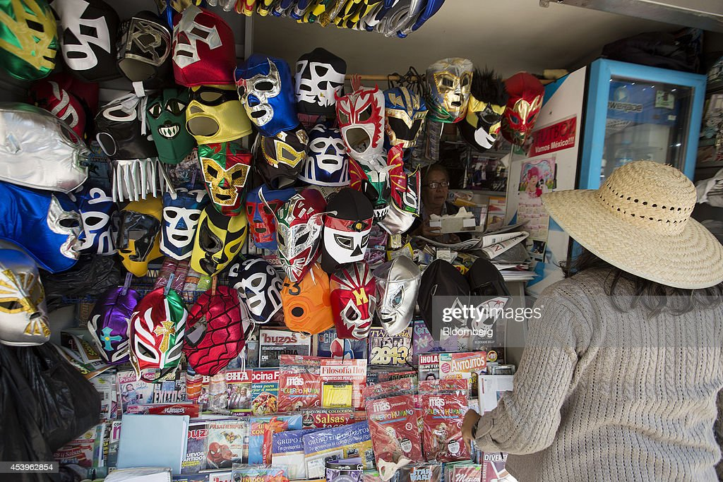 A woman selling wrestling masks, magazines and newspapers from a stall on Reforma Avenue chats with a customer in Mexico City, Mexico, on Thursday, Aug. 21, 2014. Mexican consumer prices rose more than analysts expected in the first half of August and the unemployment rate rose to 5.47 percent in July compared with 4.8 percent in June. Photographer: Susana Gonzalez/Bloomberg via Getty Images