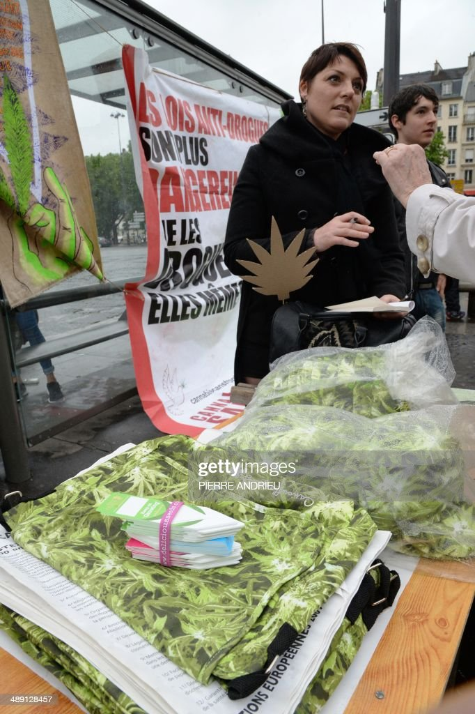A woman sells bags (L) and caps (R) on which are drawn cannabis leafs while people take part in a protest to call for the legalization of marijuana on May 10, 2014 in Paris. About 147 million people globally -- or about 2.5 percent of the population -- use cannabis, according to the World Health Organization. AFP PHOTO / PIERRE ANDRIEU