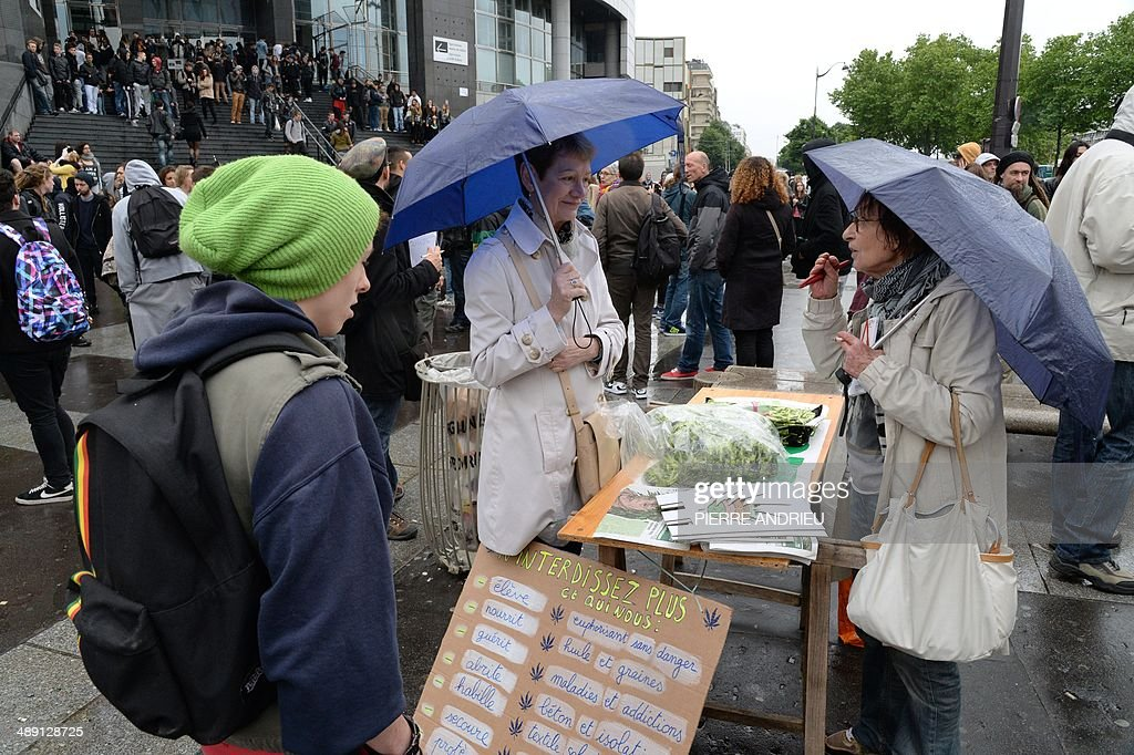 A woman (C) sells bags and caps on which are drawn cannabis leafs while people take part in a protest to call for the legalization of marijuana on May 10, 2014 in Paris. About 147 million people globally -- or about 2.5 percent of the population -- use cannabis, according to the World Health Organization.