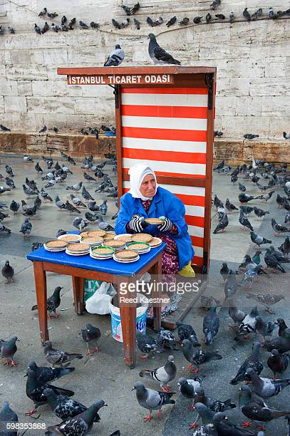 A woman sells bird feed for the pigeons in Istanbul, turkey