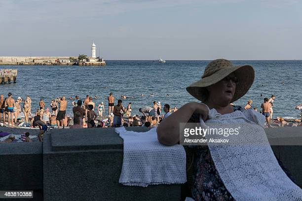 A woman sells blouses on the embankment on August 10 2015 in Yalta Crimea Russian President Vladimir Putin signed a bill in March 2014 to annexe the...