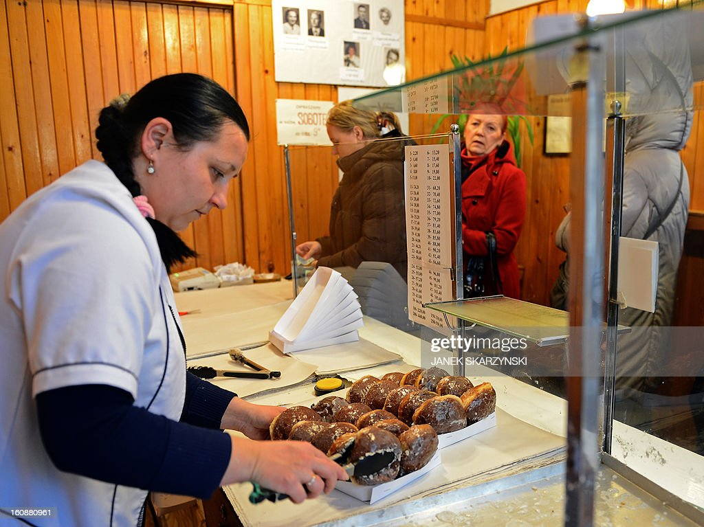 A woman sells cakes to people who stood in line for some six hours in sub-freezing temperatures in front of a popular sweet shop in Warsaw to get the cakes, jam-filled doughnut Paczki traditionally eaten on the Thursday of Carnival, the Fat Thursday on February 7, 2013.