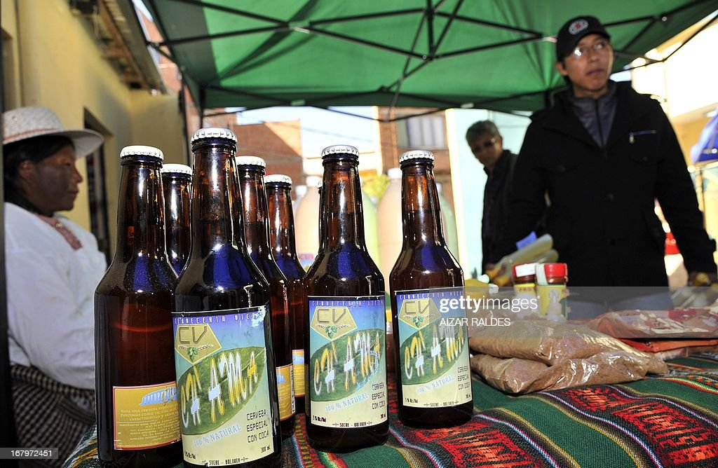 A woman sells Ch'ama, a coca leaves and barley based beer in a street market in La Paz, on May 2, 2013. The beer, made with organic barley and coca, have the same alcohol content that a normal one, and is mainly consumed by European tourists. AFP PHOTO / Aizar Raldes