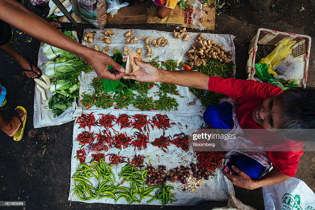 A woman sells chilli peppers and spices in the market district of Divisoria in Manila the Philippines on Monday Jan 6 2014 Philippine consumer prices...