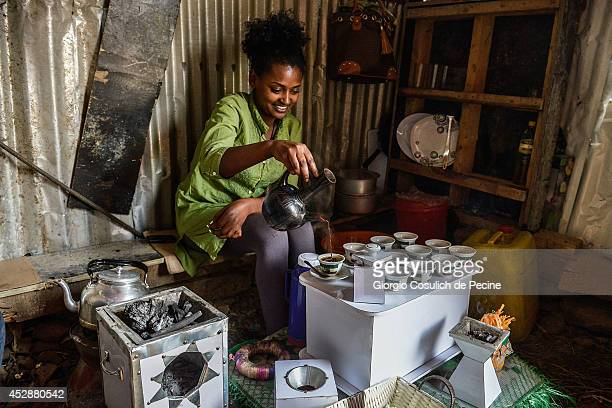 A woman sells coffee inside a hut on July 02 2014 in Addis Ababa Ethiopia The Ethiopian government has recently launched a new urban plan for the...
