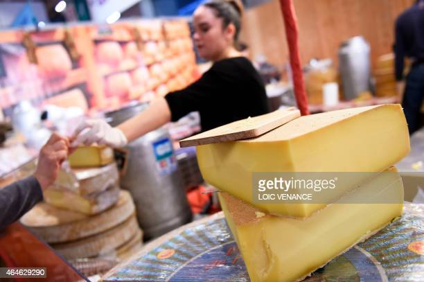A woman sells Comte cheese during the Paris international agricultural fair at the Porte de Versailles exhibition center in Paris on February 26 2015...