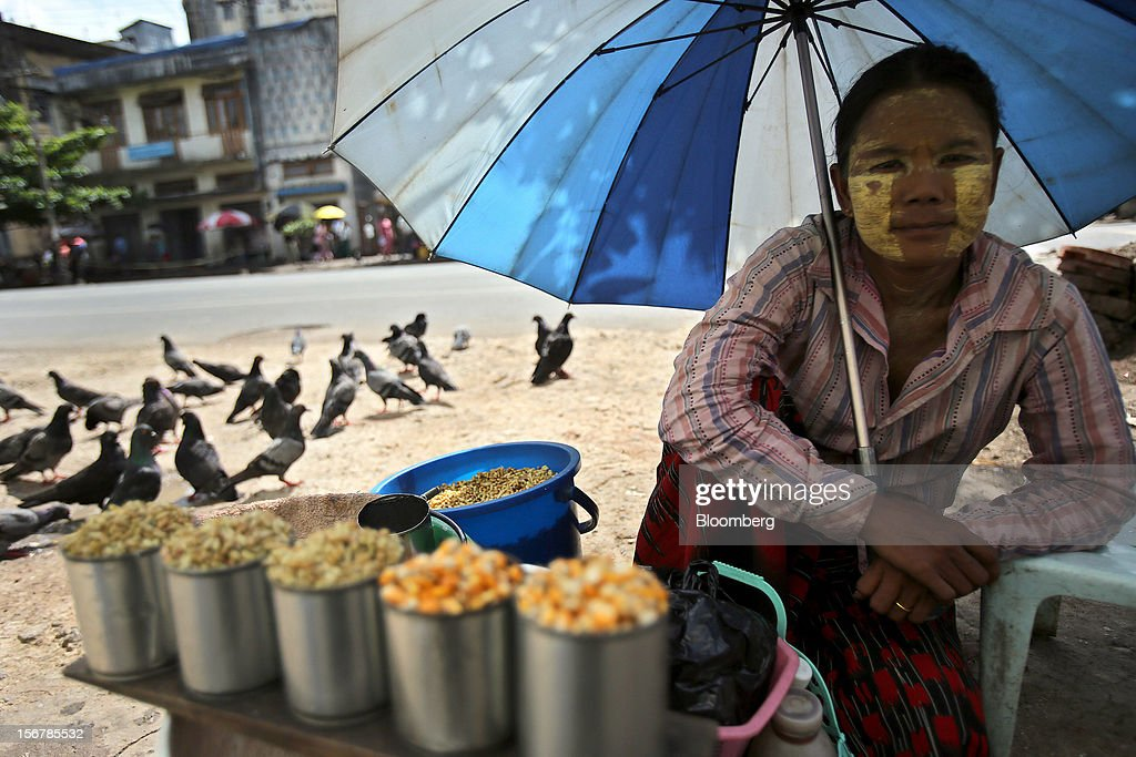 A woman sells corn to feed pigeons at a market in Yangon, Myanmar, on Tuesday, Nov. 20, 2012. Myanmar's growth outlook has improved 'substantially' amid political reforms, which are expected to lead to a large influx of foreign investment, the Organization for Economic Cooperation and Development (OECD) said on Nov. 18. Photographer: Dario Pignatelli/Bloomberg via Getty Images