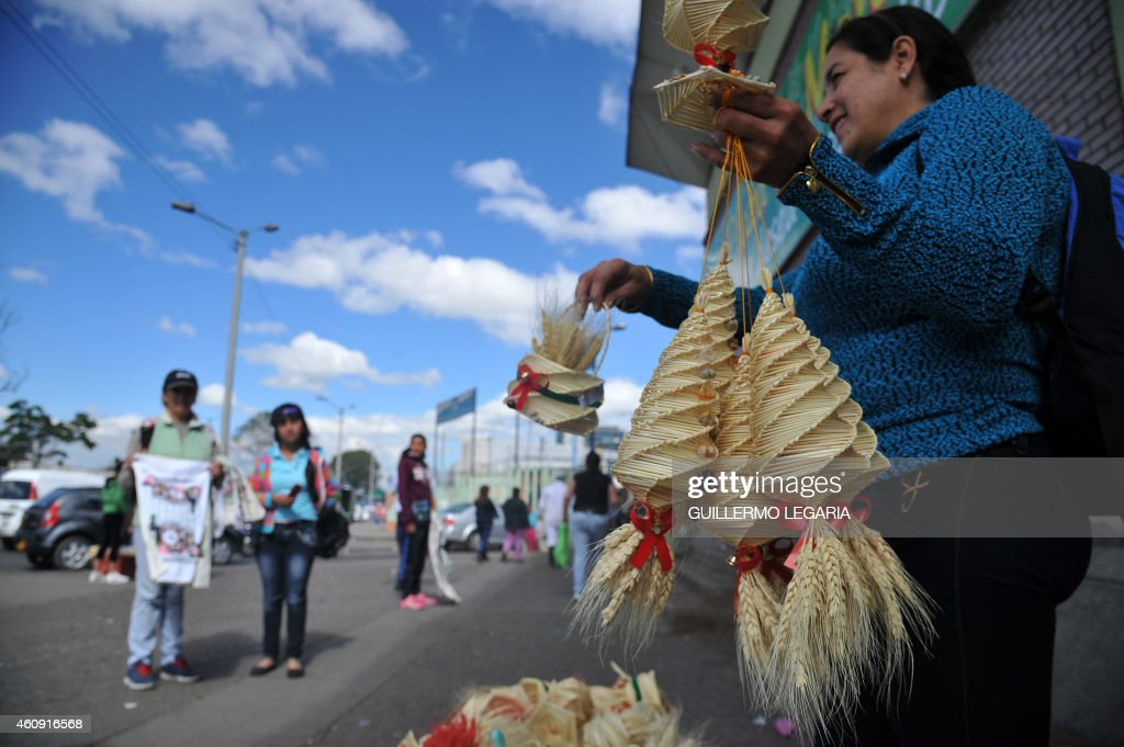 A woman sells crafts made with wheat ears, used for New Year's rituals, outside Paloquemao market in Bogota, Colombia, on December 30, 2014. In great part of Latin America, New Year is celebrated with deeply rooted omens as wheat ears and yellow flowers, herb and champagne baths, walking around the block with a suitcase, having lentils in the pocket, putting potatoes under the bed and the ritual of the 12 grapes. AFP PHOTO/Guillermo LEGARIA /