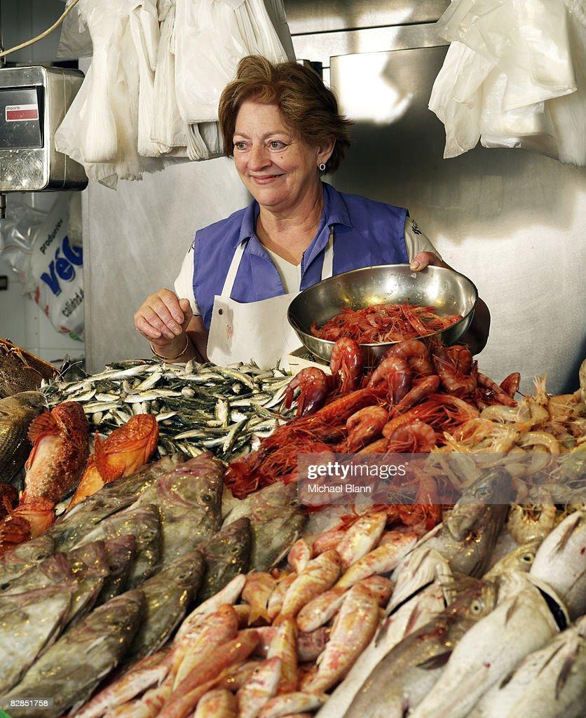 Woman sells fish at stand : Stock Photo