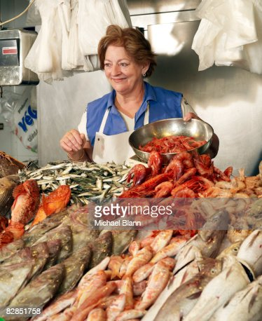 Woman sells fish at stand : Stock Photo