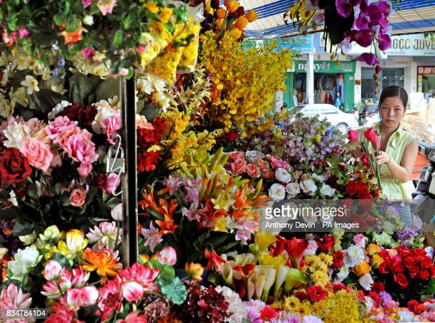A woman sells flowers in Cho Ben Thanh market in Ho Chi Minh City Vietnam