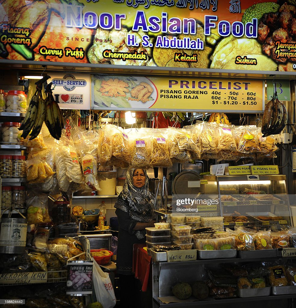 A woman sells halal food in a market in the area of Little India in Singapore, on Saturday, Dec. 29, 2012. Singapore may grapple with elevated inflationary pressures for a third year in 2013, reducing scope for the central bank to provide stimulus to an economy that probably entered a technical recession this quarter. Photographer: Munshi Ahmed/Bloomberg via Getty Images