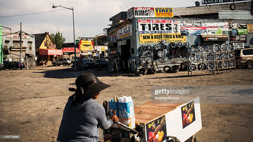 A woman sells ice cream from a pushcart to auto mechanics on June 17, 2013 in the Willet's Point neighborhood of the Queens borough of New York City. The Willet's Point Neighborhood, also known as the Iron Triangle, is situated directly next to Citi Field, where the Met's play baseball, and is known for both its car repair shops and lack of paved roads. The future of the neighborhood has been a contentious issue between residents and the city, as the city hopes to further develop the land despite protests from its residents.