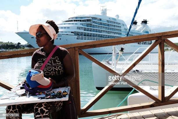 A woman sells jewelry to tourists across from a cruise ship on December 10 2017 in St John's Antiqua While it's sister island Barbuda was nearly...