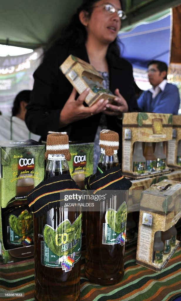 A woman sells liquor made out of coca leaves at her stall in a square of La Paz, on March 12, 2013 during the celebration of the first National year of Coca Chewing (acullicu). AFP PHOTO/Aizar Raldes