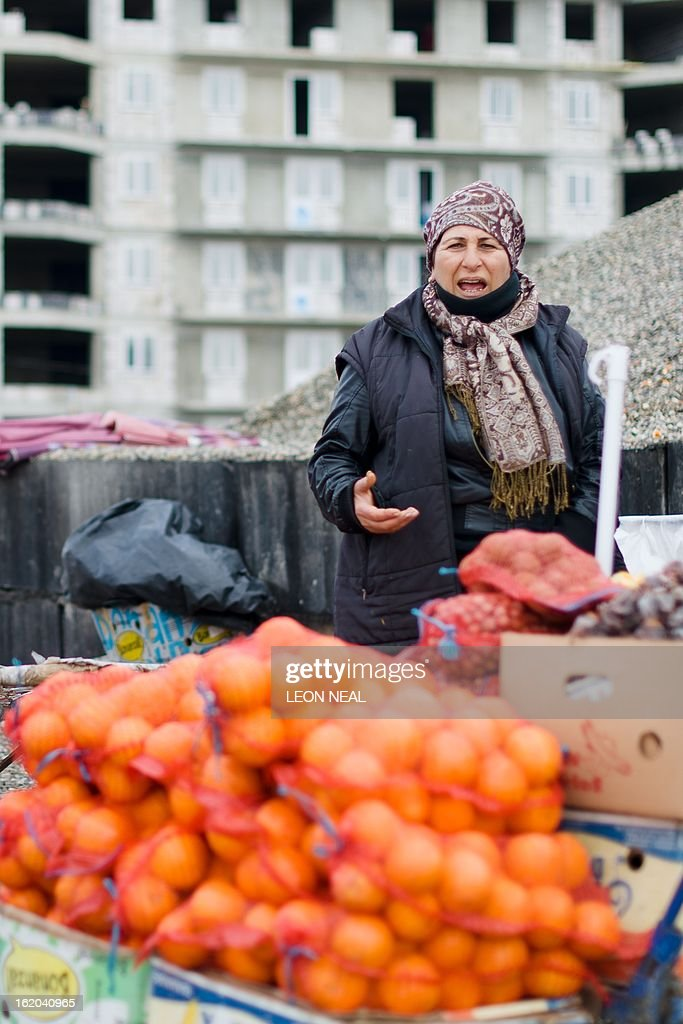 A woman sells oranges by the roadside near to a major construction project in Adler, a district of Sochi, Russia, on February 18, 2013. With a year to go until the Sochi 2014 Winter Games, construction work and development continues as Olympic tests events and World Championship competitions are underway.