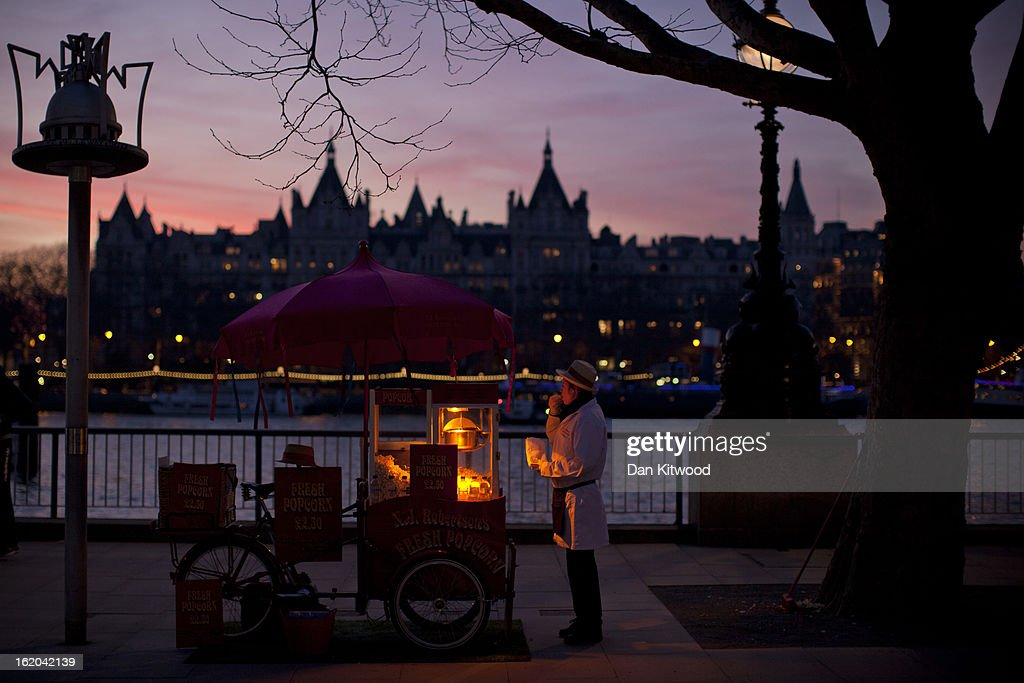 A woman sells popcorn from a traditional cart at sunset on London's Southbank on February 18, 2013 in London, England.