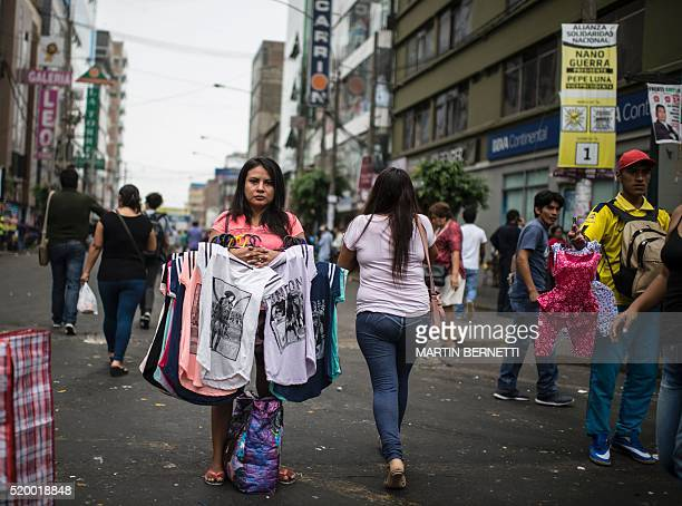 A woman sells tshirts on the street in a commercial district in Lima on April 07 2016 The textile industry in Peru which concentrates about 80% of...