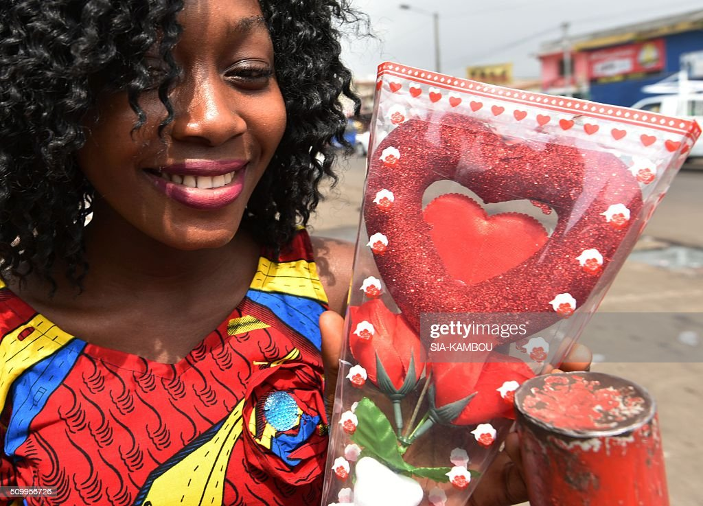 A woman sells Valentine's day items on February 13, 2016 in a street market in Marcory, a popular suburb of the Ivorian capital. / AFP / SIA-KAMBOU