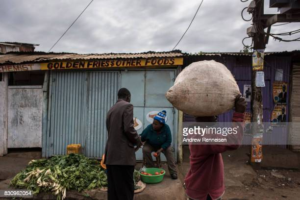 A woman sells vegetables in the Kibera slum on August 13 2017 in Nairobi Kenya A day prior demonstrations turned violent in some areas throughout...