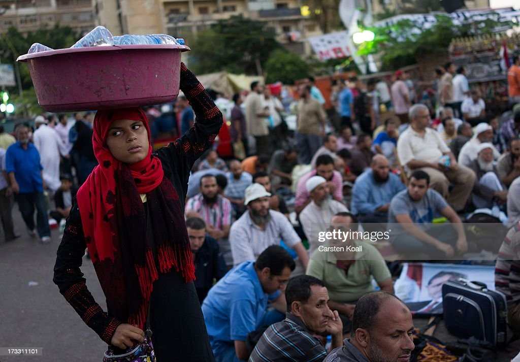A woman sells waterbottles as supporters of ousted president Mohamed Morsi pray before breaking the daily Ramadan fast on the second day of Ramadan...
