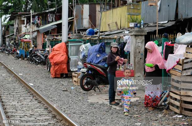 A woman sellsing drinks on her bicycle stands next to a veiled Muslim woman with her kid by the rairoad track in Kota City on November 25 2016 in...