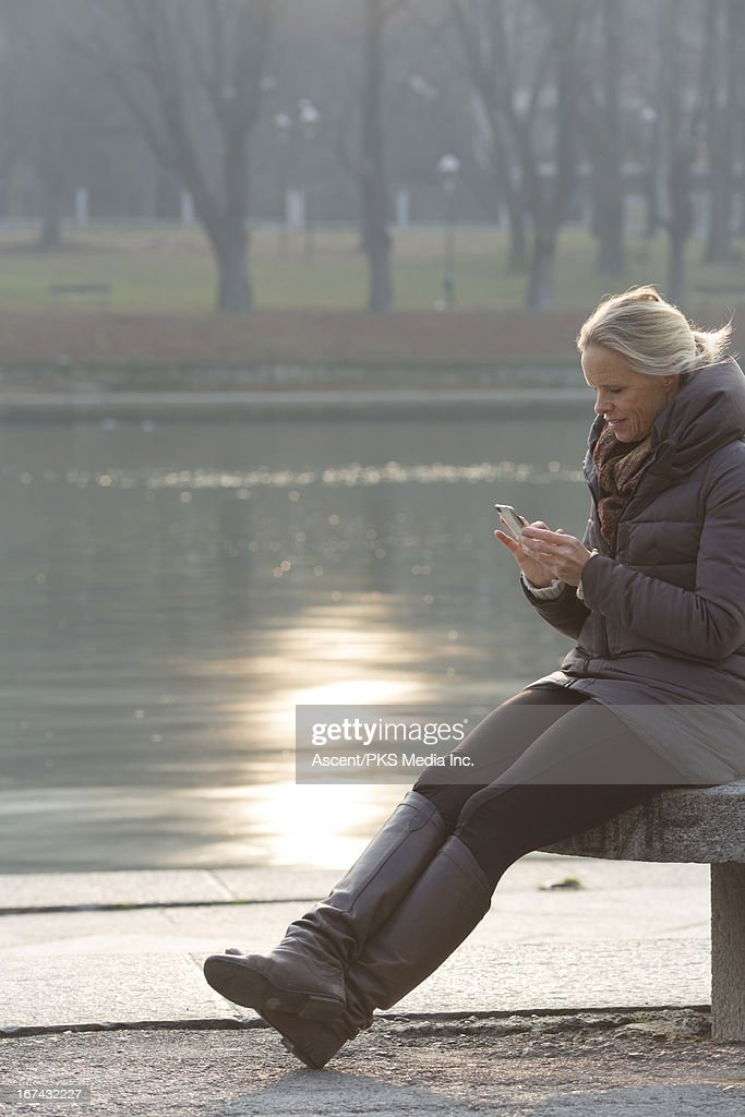 Woman sending text from bench by river's edge : Foto de stock