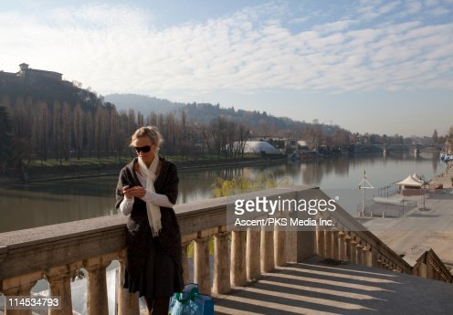 Woman sending text message beside river : Stock Photo