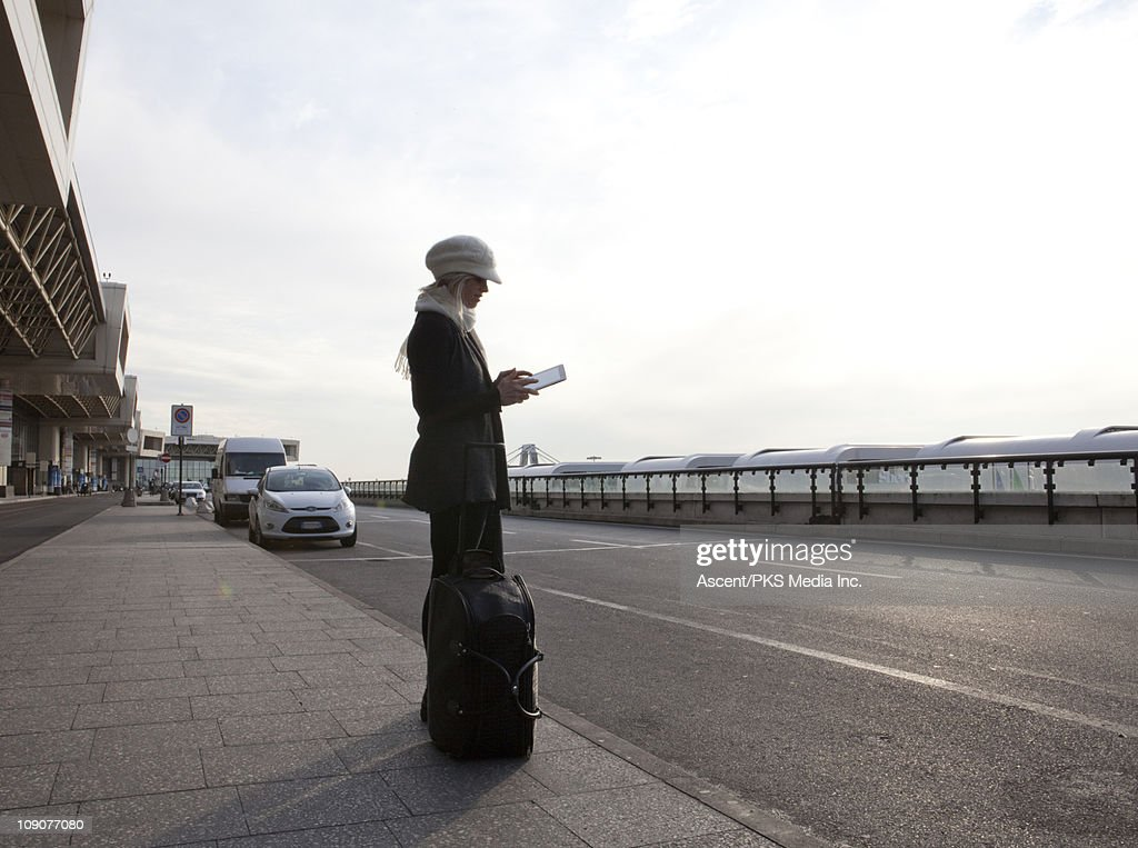 Woman sends message on digital tablet, outside airport : Stock Photo