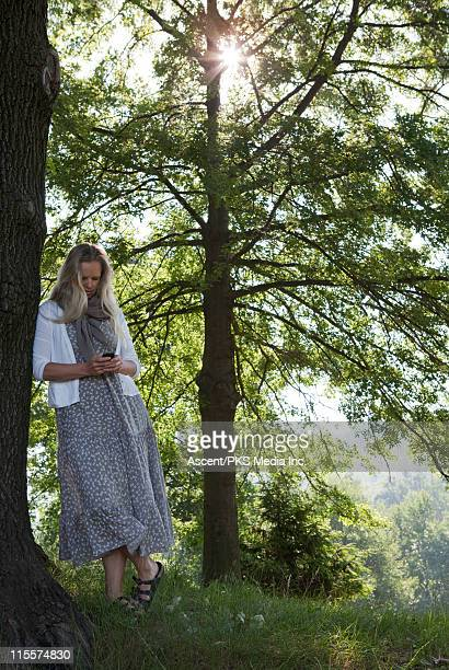 Woman sends text message, under tree in park
