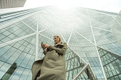 Woman sends text on smart phone, city center