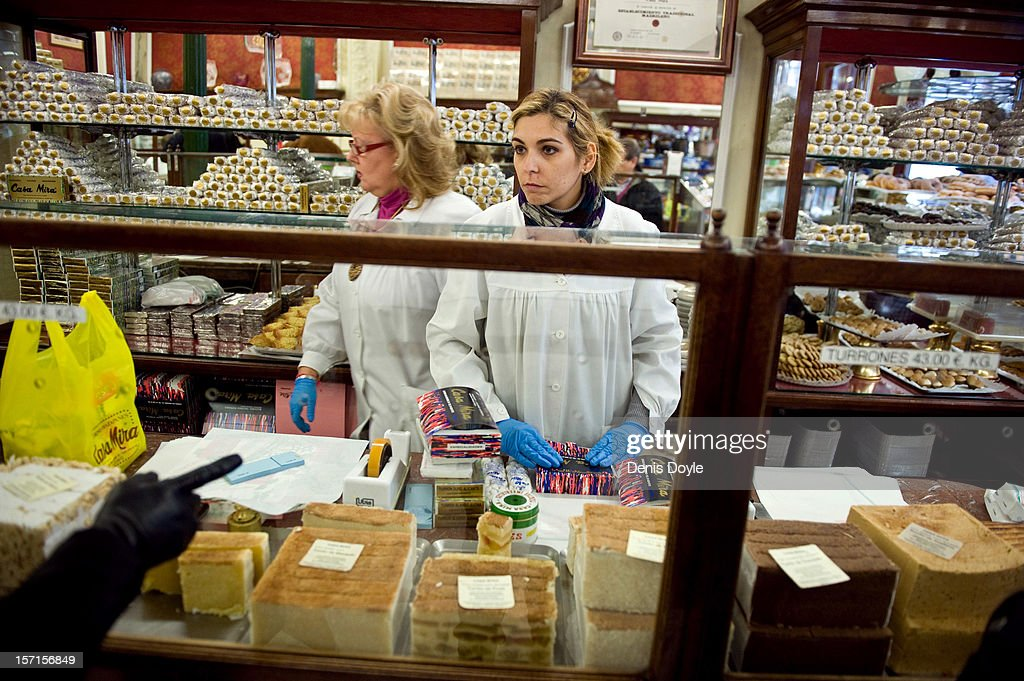 A woman serves a customer a traditional almond-based turron cake at the Casa Mira cake shop on November 29, 2012 in Madrid, Spain. Spanish businesses are hoping for a pick-up in consumption over the usually busy christmas period employing extra workers.
