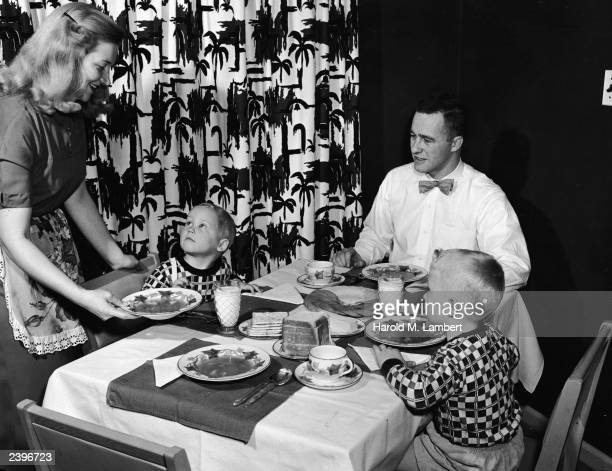 A woman serves soup to her family a man wearing a bow tie and two young boys sit at the dinner table 1940s