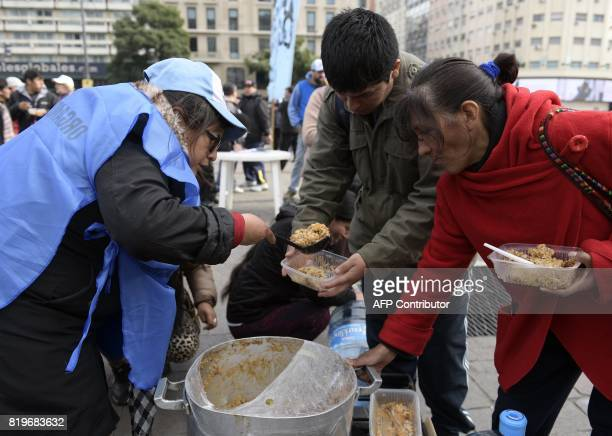 A woman serves stew from a soup kitchen during a protest by activists from social organizations against the economy policy of Argentina's President...