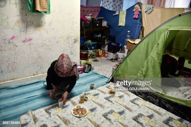 A woman serves tea at the compound where she lives during the celebrations of Nauroz 'New day' the traditional Afghan New Year's Day on March 21 2017...