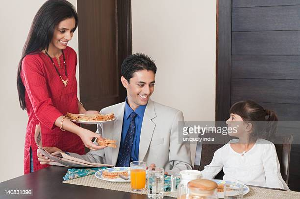 Woman serving breakfast to her family