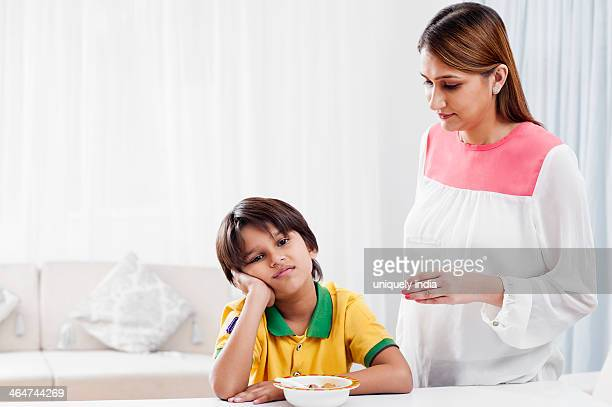Woman serving breakfast to her son