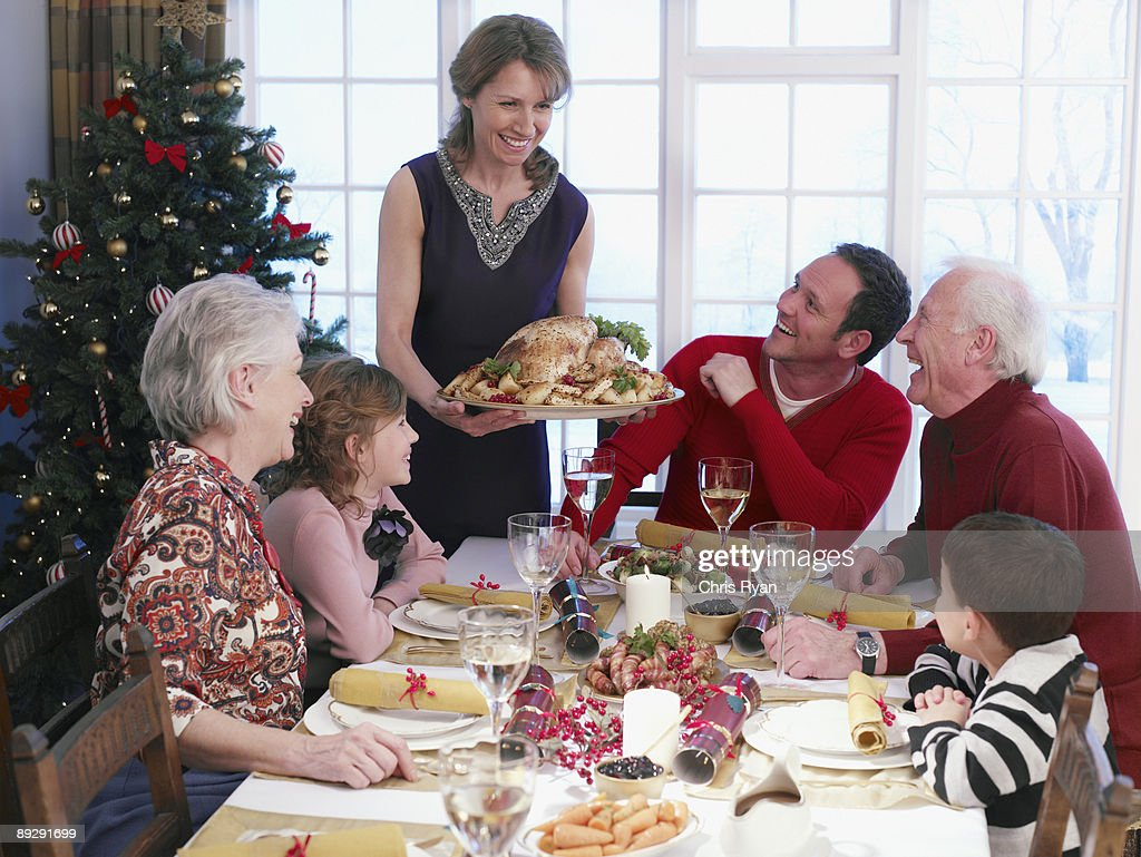 Woman serving Christmas turkey to multi-generation family at table : Stock Photo
