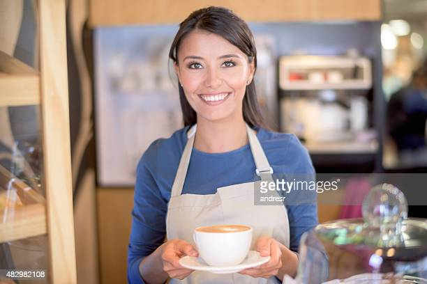 Woman serving coffee at a cafe