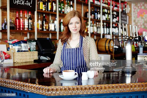 Woman serving coffee in bar.