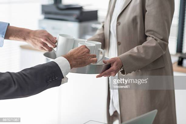 Woman serving coffee on a tray in office