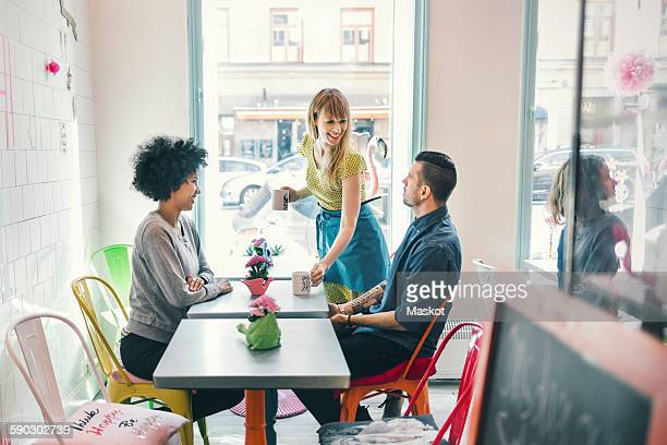 Woman serving coffee to customers in coffee shop