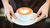 woman serving coffee while standing in coffee shop. Focus on Latte art hearth shape cup in female hands while placing of coffee on counter