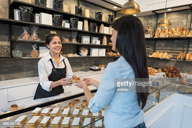 Woman serving customer at a pastry shop