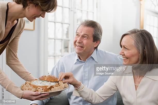 Woman serving dip to parents