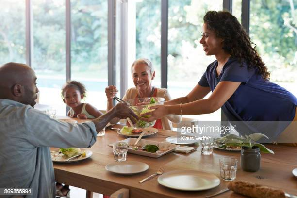 Woman serving food, at family dinner